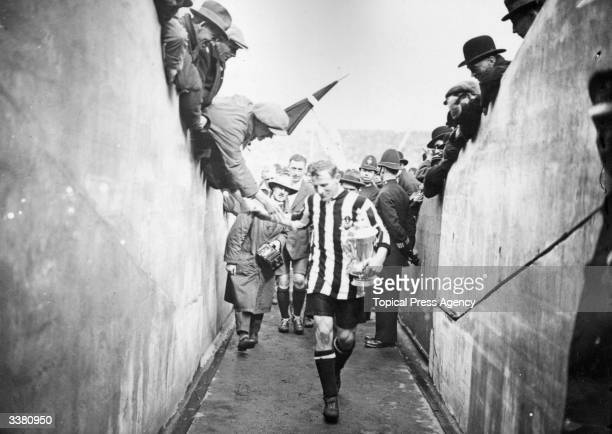 Newcastle United FC full back Frank Hudspeth carries the FA Cup trophy back down the players tunnel after the presentation and celebrations of...