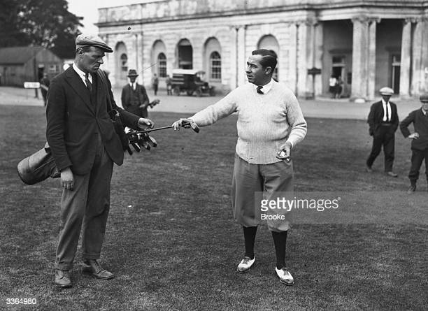 Golfer Walter Hagen takes a club from his giant caddie J W Williams who is 6ft 2'' tall during practice for the round against Archie Compston at...