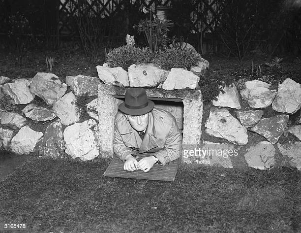 Airraid warden Irvin A McGraw in the emergency exit of the concrete airraid shelter which he built in his garden rockery The shelter was opened to...
