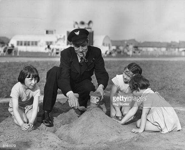 Airport Foreman Mr G Mannering lends a hand whilst 9yearold Jean Hemmings eightyearold Gillian Saunders and fiveyearold Susan Thomas build sand...