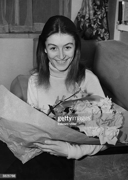 French actress Anouk Aimee with a bouquet of flowers after arriving at the Athenaeum Court, Piccadilly, London, where she is to take part in the...