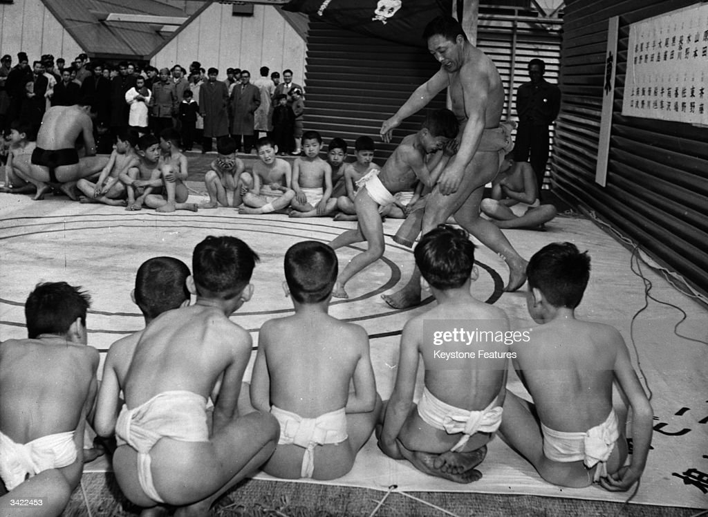 A pupil in a sumo wrestling class beating his teacher in a match while the other boys watch.