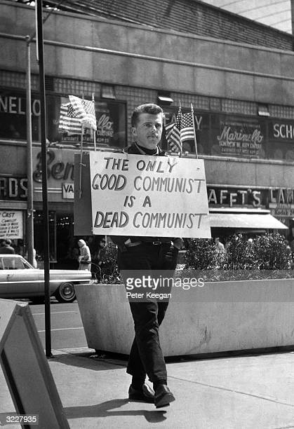 New York nightclub owner Jack L Hickman spends his free time marching around Times Square with a sign that reads 'The only good communist is a dead...