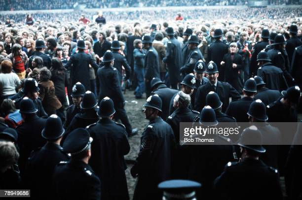 26th April 1975 Old Trafford Manchester Division Two Manchester United 4 v Blackpool 0 Policemen attempt to restore order after a pitch invasion...