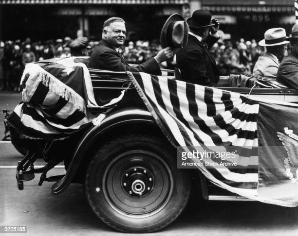 President Herbert Hoover waves his hat in recognition of the crowds surrounding his car in a parade, San Francisco, California.