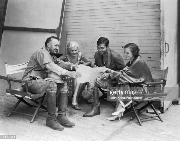 Actors Donald Crisp, Jean Harlow, Clark Gable and Mary Astor are amused by the script during the making of the film 'Red Dust', directed by Victor...
