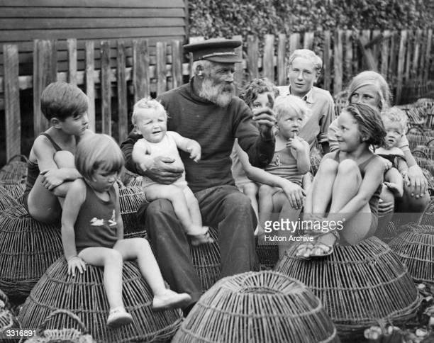Children gather round to listen to a fisherman's tales, at Felpham, near Bognor Regis.