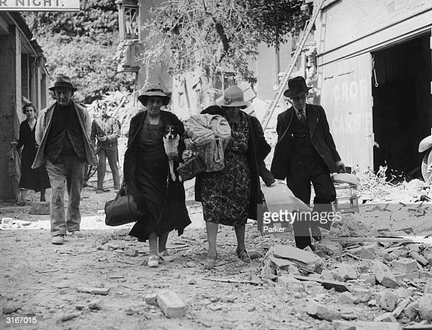 Mrs Fagg and Miss Horsley carrying away some of their belongings including their pet dog and canaries after their homes were destroyed in German...