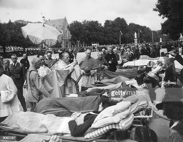Ceremony of blessing the sick at Lourdes with a priest holding a monstrance as he conducts a service at the foot of a row of stretchers