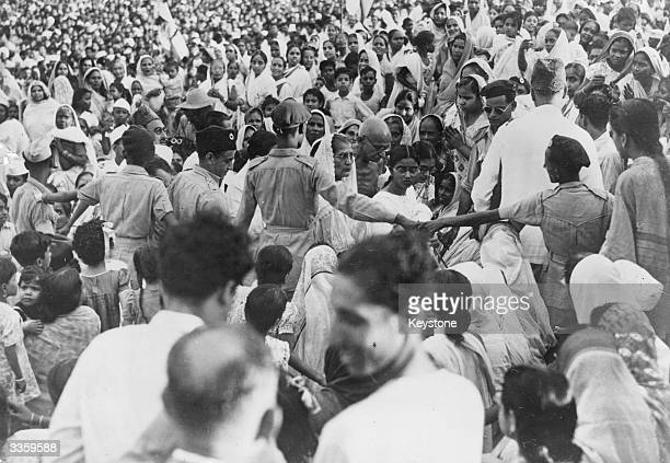 Indian Nationalist leader Mahatma Gandhi arriving through a surging crowd for a prayer meeting on the Calcutta Maidan India 100000 Hindus and Muslims...