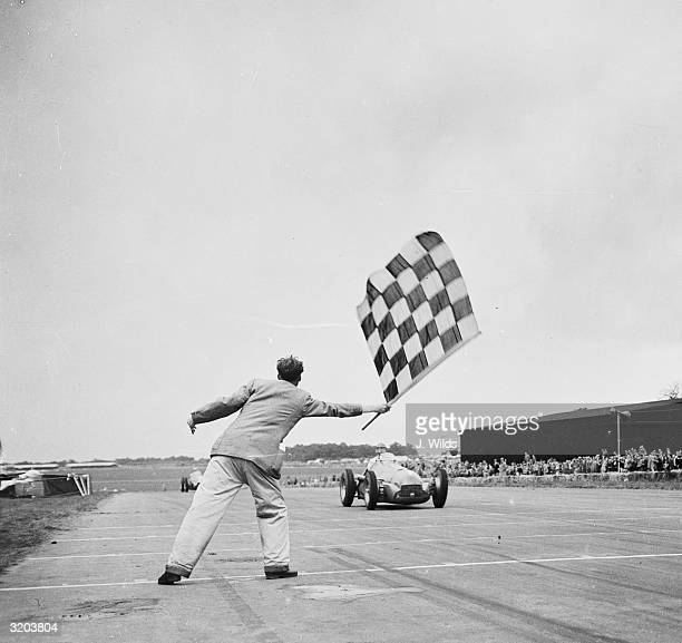 Giuseppe Farina driving for Alfa-Romeo is flagged as he crosses the finishing line to win the International Trophy Race at Silverstone.