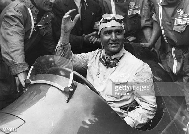 Italian racing driver Giuseppe Farina acknowledges the cheers of the spectators from his AlfaRomeo after winning the International Trophy Race at...