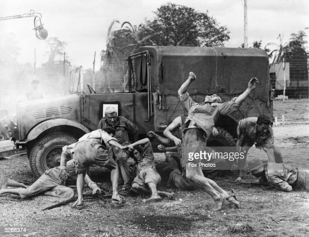 Actors playing the roles of prisoners and guards during the filming of a battle scene for the film 'The Camp On Blood Island' which tells the story...
