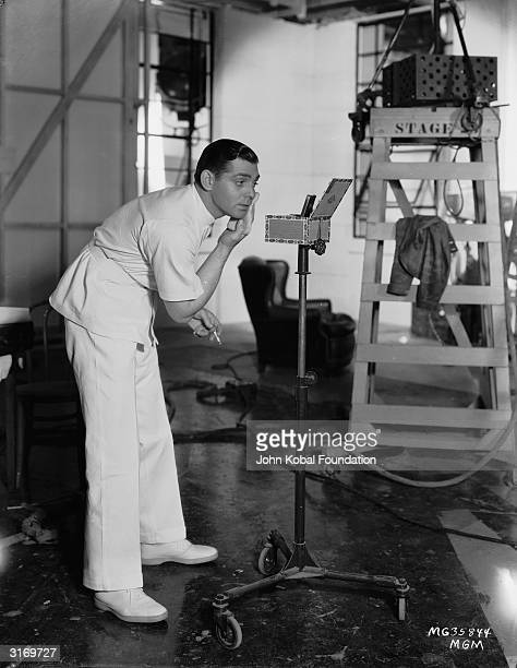 American actor Clark Gable applying his makeup during the filming of 'Men In White' in which he plays a young doctor whose dedication to his job...