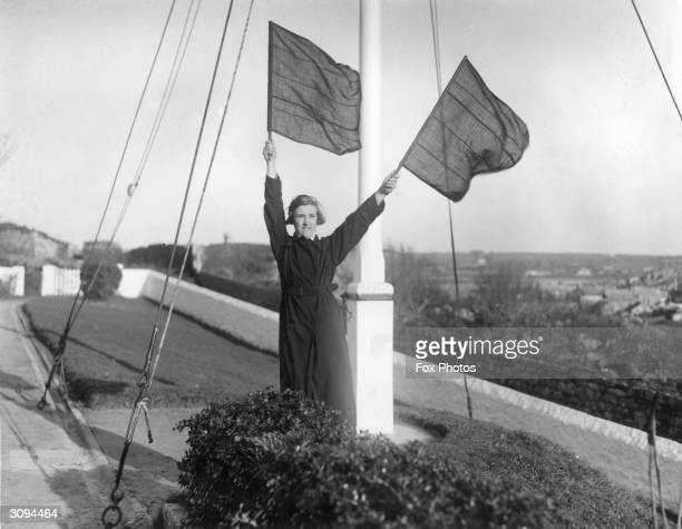 The lighthouse keeper's daughter uses semaphore to signal that the relief boat has returned safely from the Bishop Rock Lighthouse in the Scilly...