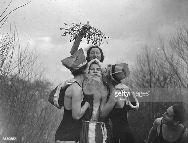 Father Christmas getting a kiss under the mistletoe from swimmers at the Kenwood Ponds on Hampstead Heath London