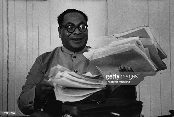 Crown Prince Tungi of Tonga, holding a pile of paperwork in his hand. Original Publication: Picture Post - 6832 - Report From Tonga - pub. 1953