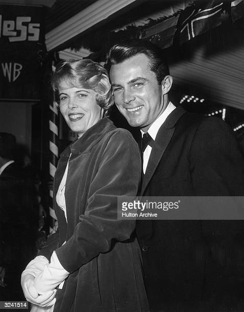American actor Robert Conrad and his wife Joan Kenly stand together and smile outside the Village Theater after the premiere of director Mervyn...