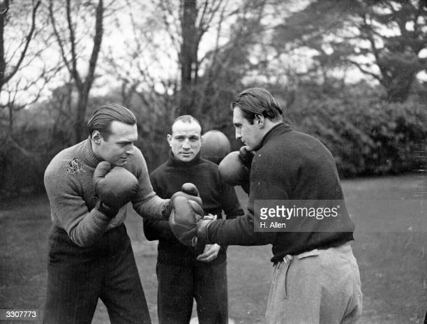 Sir Arthur Conan Doyle's sons Adrian Doyle and Denis Doyle receiving instruction from boxer Johnny Brown as part of their fitness training for a...