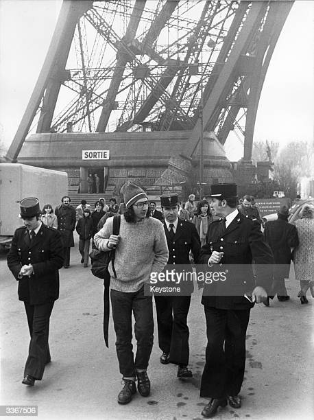 American Doug Allen with a group of Gendarmes after climbing to the second stage of the Eiffel Tower to unfurl a 'Save Baby Seals' banner he was...