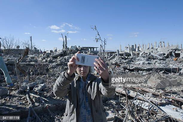 Year-old Giana Mustafa takes a selfie amongst the rubble of her home in Kobani, Syria, on her return from a refugee camp in Turkey.