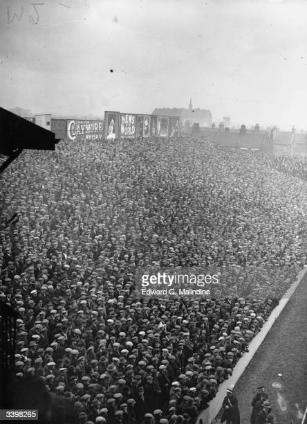 Crowds of hatwearing football fans at a cup tie match between West Ham United and the Corinthians at Upton Park
