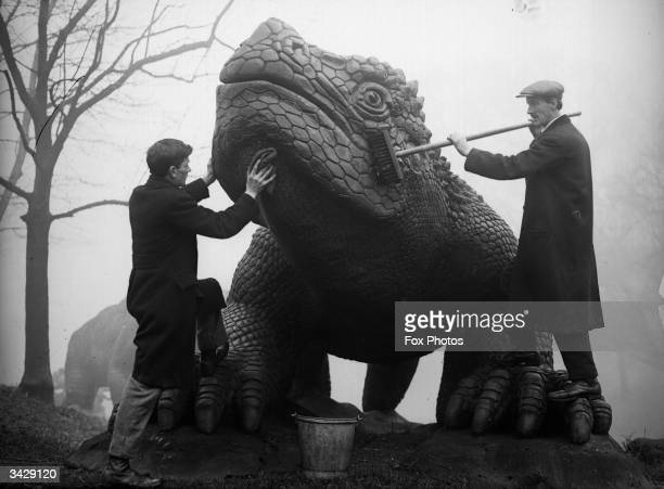 Exhibition staff give a prehistoric model its annual clean in the grounds of Crystal Palace in London
