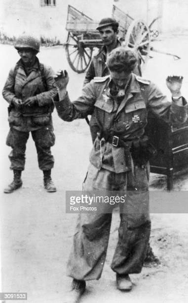 A German officer wearing an Iron Cross surrenders to Allied soldiers in Tunisia during World War II