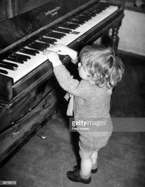 Michael Holden aged 22 months stretches to reach the keys of a piano at the Mary Ward Nursery where children are looked after whilst their mothers do...