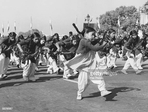 A group of young girls playing instruments and dancing during a march past to celebrate India's 11th Republic Day in Delhi
