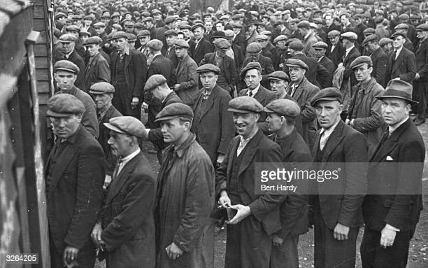 Hundreds of dockers line up to collect their pay Original Publication Picture Post 816 The Truth About The Dockers pub 1941