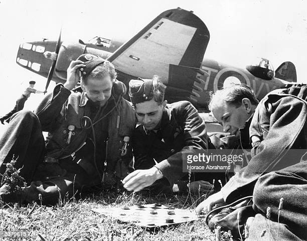 Three of the crew of a Lockheed Hudson of the 206 Squadron based at St Eval in Cornwall playing a game of draughts in front of their aircraft Their...