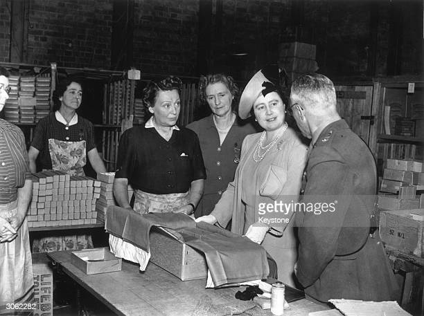 Her Majesty Queen Elizabeth visita a forces' comforts depot where voluntary workers pack comforts and amusements to be sent to troops serving on the...