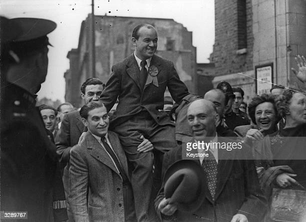 Communist MP Phil Piratin is chaired by supporters after winning an election in Mile End London