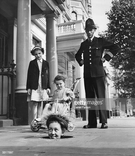 Former child actress Janette Scott emerges from a coal hole wearing one of Kensingtonbased designer Geynne Mallard's hats to the interest of a...