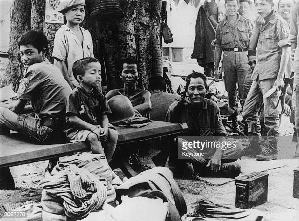 Little boy sits with his eyes closed surrounded by Cambodian government troops who are waiting to go into action during the last days before the fall...