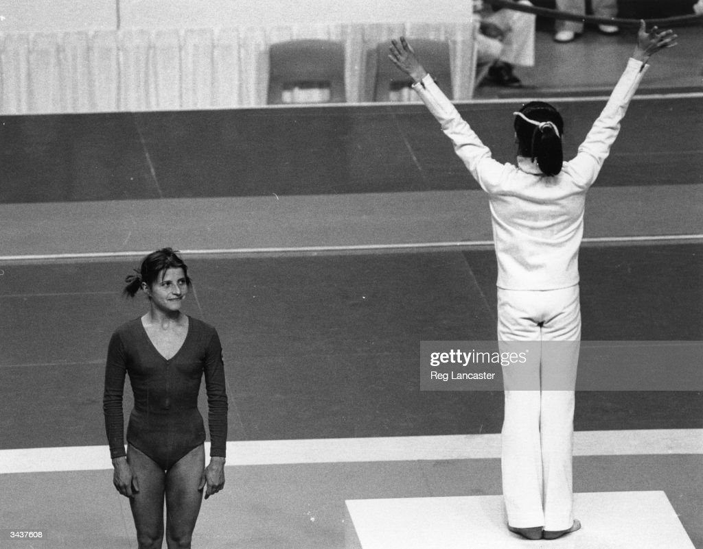 Romanian athlete Nadia Comaneci celebrating her gold medal for the beam at the Montreal Olympics, while the silver medal winner and Russian athlete Olga Korbut looks on.