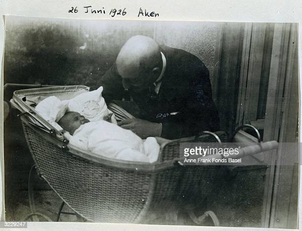 EXCLUSIVE The grandfather of Anne Frank Abraham Hollander leans over her sister Margot in a bassinet Aachen Germany Taken from Anne Frank's photo...