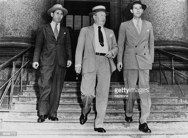 American lawyer and government official Alger Hiss leaving a New York court with his lawyers during his trial for treason where he was accused of...