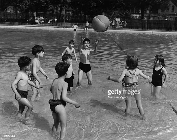 A group of children keeping cool playing with a beach ball in Southwark Lido