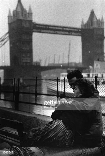 A couple of young lovers embrace on a bench beside the River Thames with Tower Bridge in the background Original Publication Picture Post 7188 The...
