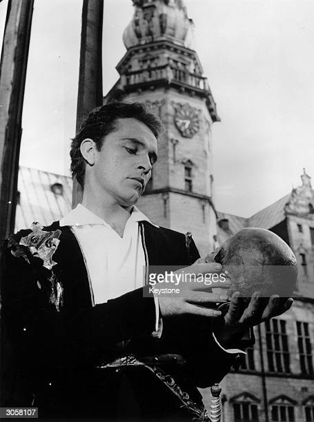 Welsh actor Richard Burton contemplates a skull at Kronberg Castle Elsinore where he and the Old Vic Company are staging a performance of...