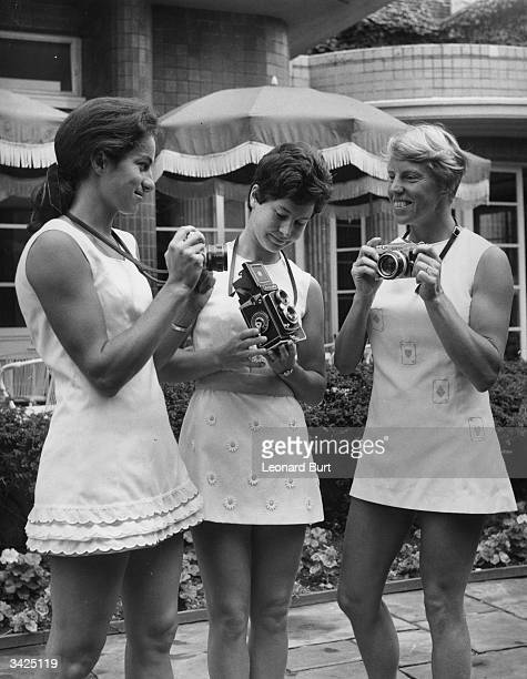 Three British tennis players holding cameras whilst showing off Teddy Tinlings sports collection for Wimbledon Virginia Wade left wears a 'dacron'...