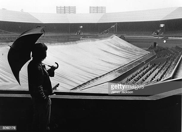 A lone spectator looks out over the Centre Court at Wimbledon where the start of play has been delayed due to heavy rain