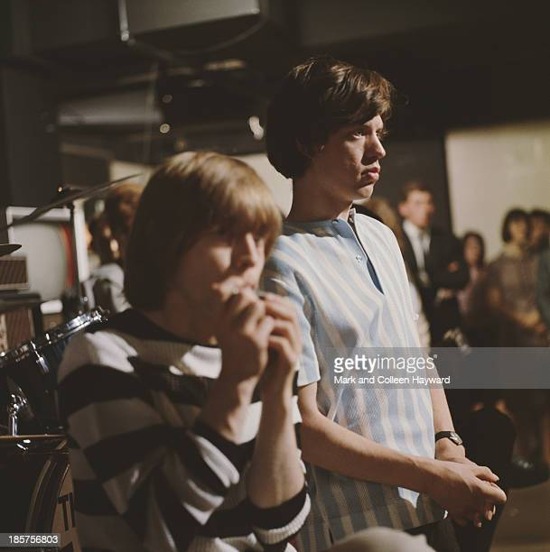 Brian Jones and Mick Jagger from The Rolling Stones posed on the set of the 'Ready Steady Go' TV show at Television House London on 26th June 1964