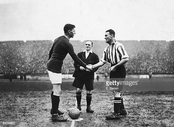Arsenal captain Charlie Buchan shakes hands with Southampton captain Harkus before the start of their FA Cup semi-final match at Chelsea.