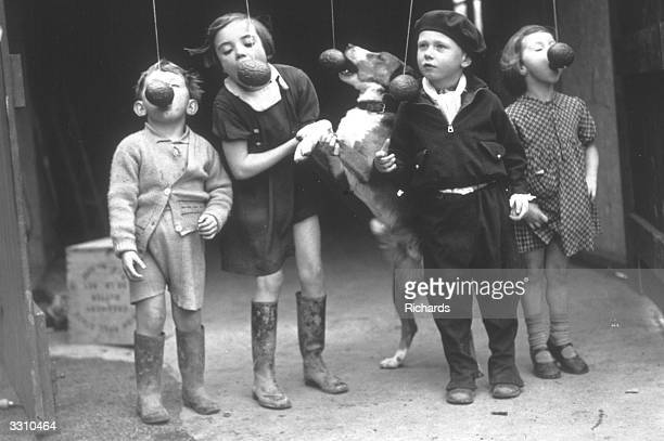 A group of children and their dog playing an Easter game in Cardiff The game involves trying to eat an Easter egg off a piece of string without using...