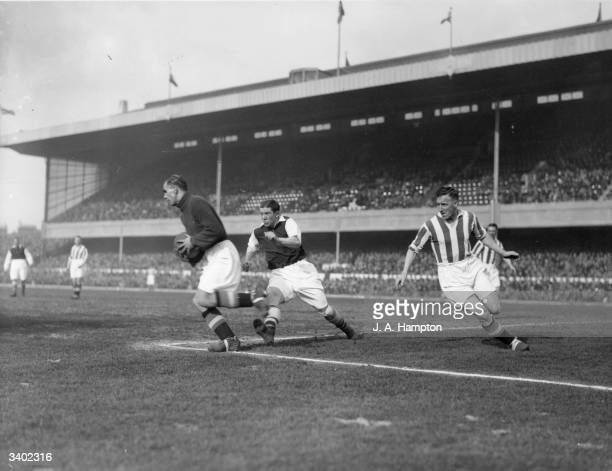 Stoke goalkeeper Wilkinson takes the ball ahead of the onrushing Ted Drake of Arsenal as Arsenal play Stoke City at Highbury