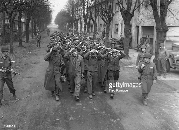 A group of German prisoners captured at Friedrichsfeld are marched through a town in Germany after the crossing of the Rhine by the US 9th Army
