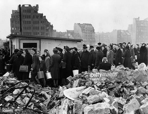 Citizens of Hamburg queuing among the ruins for their soup rations They have pails and buckets as each recipient is allowed rations for five people